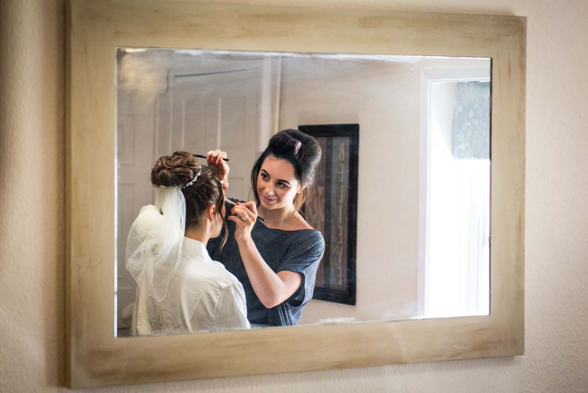 reflection of bride having her makeup done before her wedding