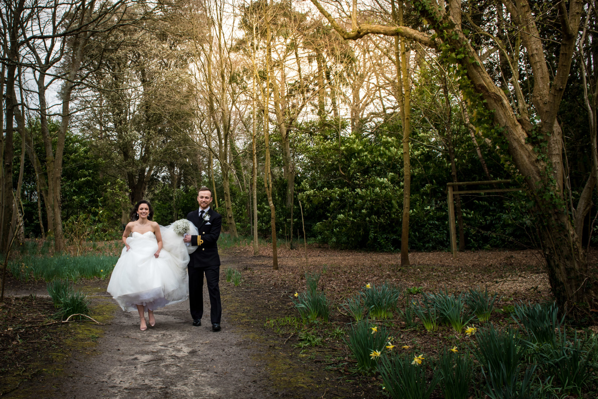 bride and groom walking in the woods on their wedding day