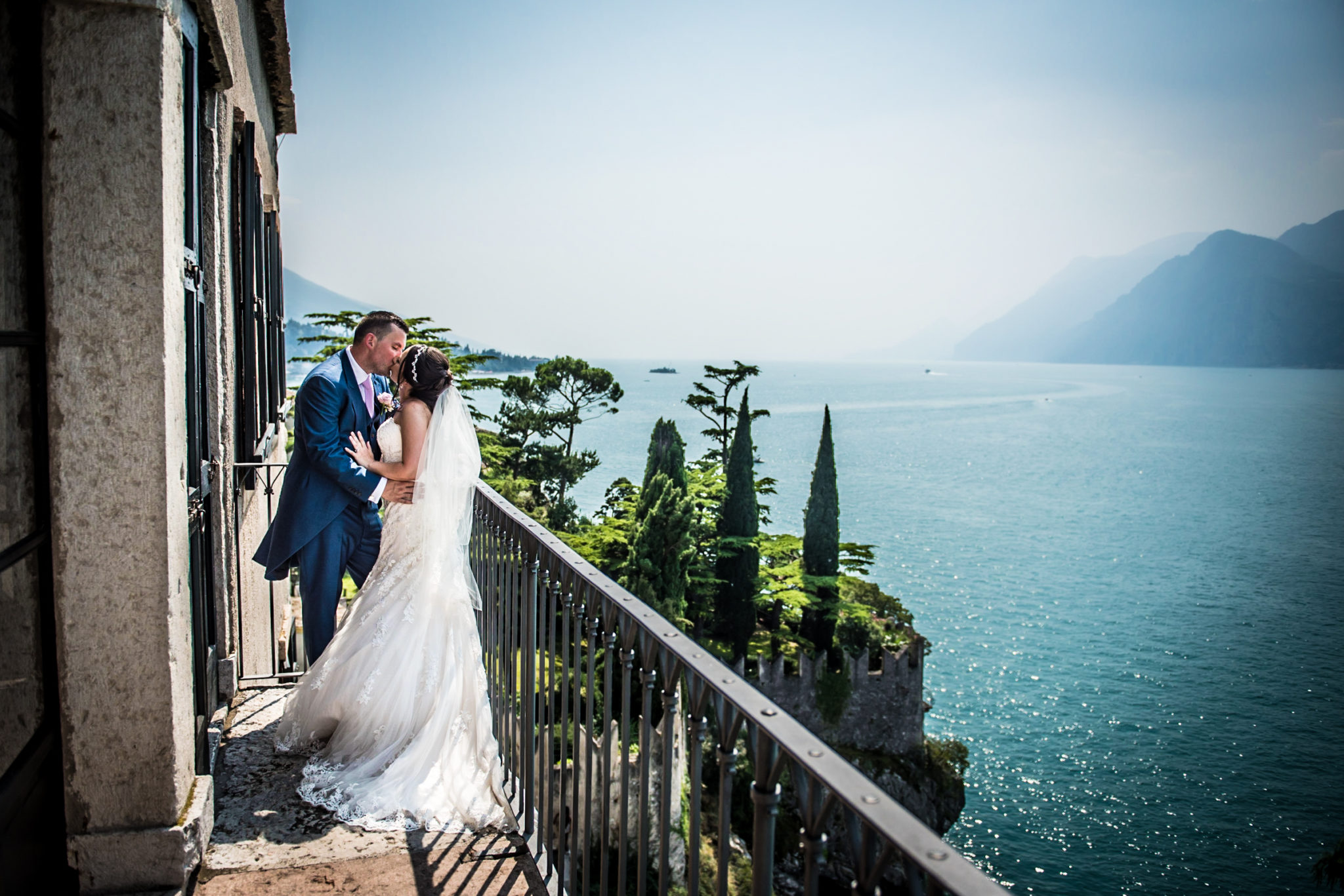 bride and groom kiss at malcesine castle overlooking lake Garda